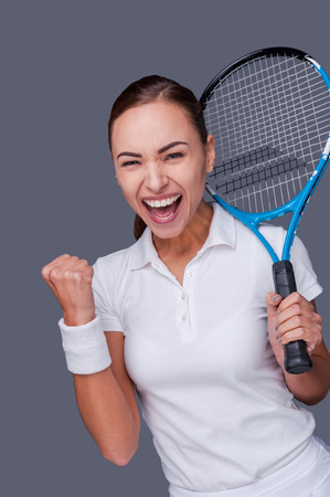 victory stand: Victory is in my pocket! Portrait of a beautiful young woman cheering while holding her tennis racket on her shoulder