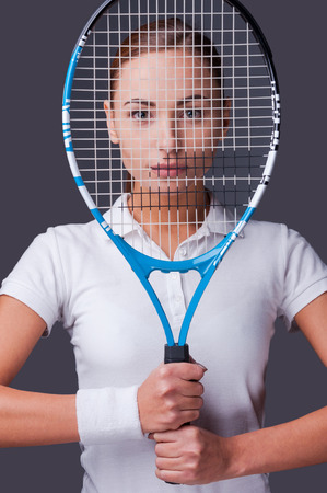 know how: I know how to win! Beautiful young women in sports clothes holding tennis racket in front of her face and looking at camera while standing against grey background