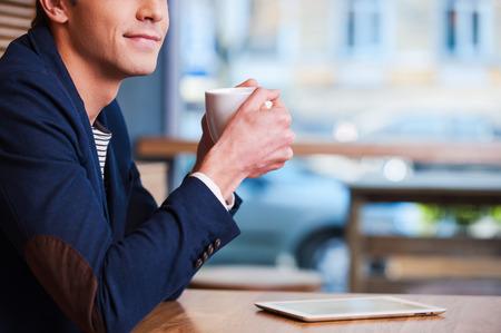 hombre tomando cafe: Tiempo de café. Vista lateral recortada imagen de hombre joven disfruta de un café en la cafetería guapo mientras se está sentado en la mesa con la tablilla digital que se cerca de él