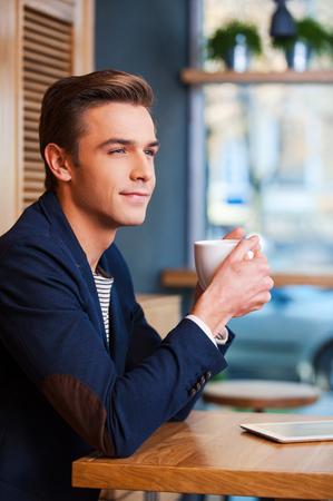 hombre tomando cafe: Inspirado por taza de caf� reci�n hecho. Vista lateral del hombre joven hermoso que goza del caf� en la cafeter�a mientras se est� sentado en la mesa con la tablilla digital por la que se cerca de �l