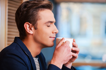 man drinking coffee: Enjoying the best coffee in town. Side view of handsome young man keeping eyes closed and smiling while smelling cup of fresh coffee in cafe Stock Photo