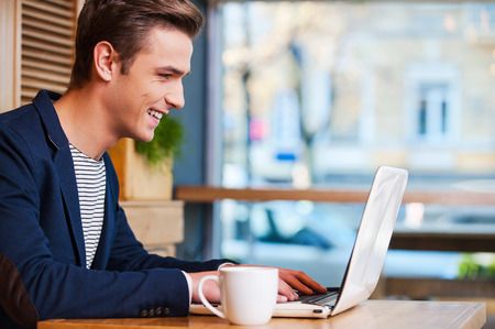 man drinking coffee: Surfing the net in cafe. Side view of handsome young man working on laptop and smiling while enjoying coffee in cafe Stock Photo