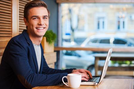 bel homme: Aucune minute sans mon ordinateur portable. Beau jeune homme travaillant sur ordinateur portable et souriant en savourant du caf� dans le caf� Banque d'images