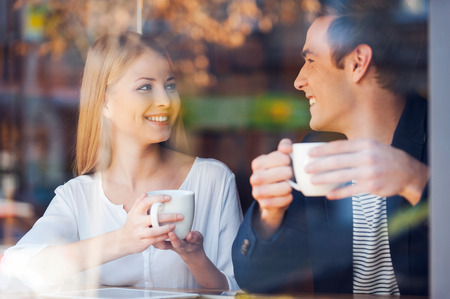 man coffee: Enjoying fresh coffee together. Through a glass shot of beautiful young couple looking at each other and smiling while enjoying coffee in cafe together