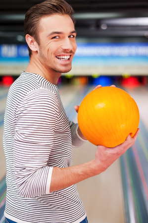 over shoulders: Hoping for a strike. Cheerful young man looking over shoulders and holding a bowling ball while standing against bowling alleys