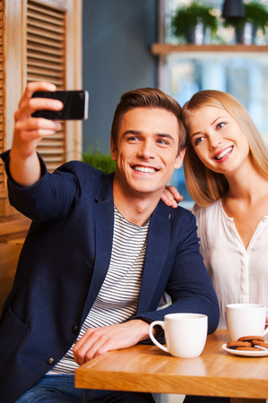 Beautiful young loving couple bonding to each other in cafe while man making selfie by smart phone photo