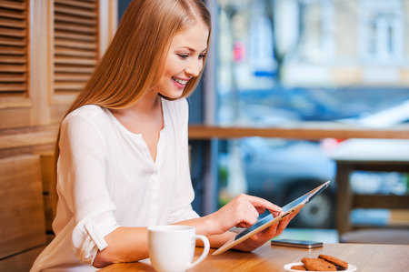 Side view of beautiful young woman using digital tablet and smiling while enjoying coffee in cafe photo