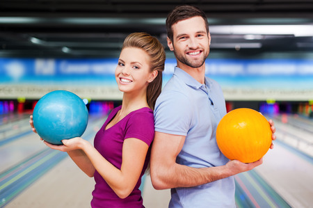 bowling ball: Cheerful young man and woman looking over shoulders and holding bowling balls while standing against bowling alleys