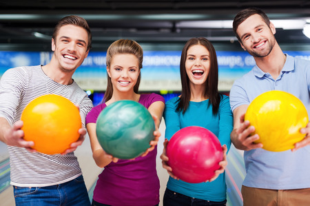Cheerful friends looking at camera and outstretching their balls while standing against bowling alleys