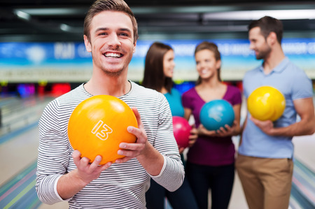 Handsome young man holding a bowling ball while three people communicating against bowling alleys 스톡 콘텐츠