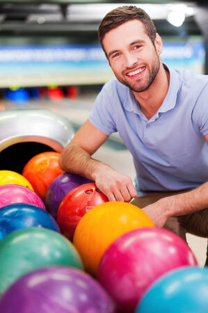 Cheerful young man sitting near bowling balls and smiling against bowling alleys Фото со стока - 33558831