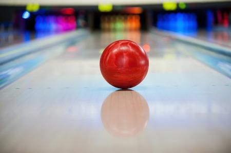 Close-up van heldere rode bowling bal aan het rollen langs bowlingbaan