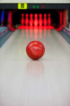 Moment when the heart stops beating. Close-up of bright red bowling ball rolling along bowling alley