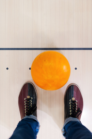 bowling alley: Close-up of a bowling ball lying near human legs Stock Photo