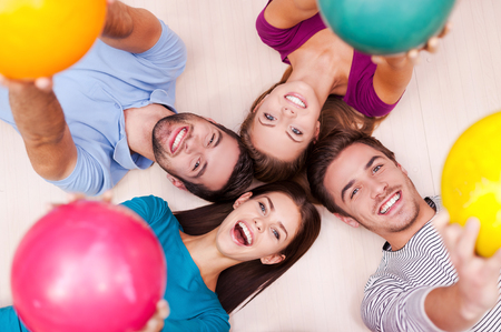outstretching: We are happy together. Cheerful friends lying down and outstretching their bowling balls Stock Photo