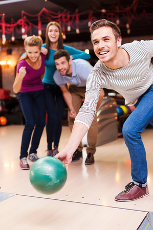 He is ready to win. Handsome young men throwing a bowling ball while three people cheering