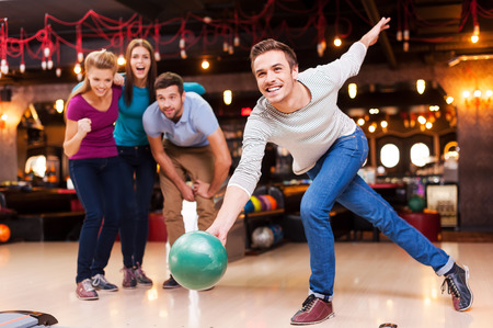 bowling pin: He is a winner. Handsome young men throwing a bowling ball while three people cheering