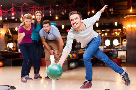 people together: �l es un ganador. Hombres j�venes guapos lanzando una bola de boliche mientras que tres personas vitoreando Foto de archivo