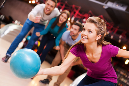 She loves this game. Beautiful young women throwing a bowling ball while three people cheering
