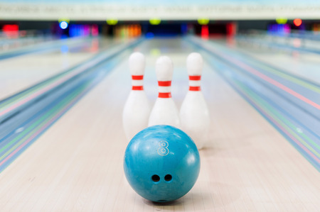 bowling pin: Close-up of blue bowling ball lying against pins staying on bowling alley Stock Photo