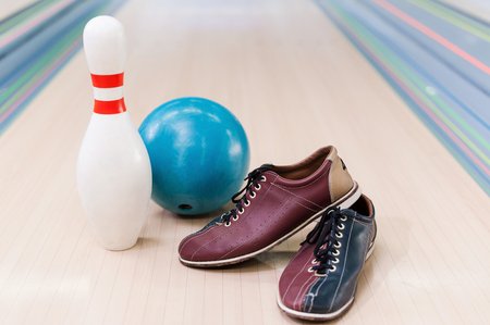 Close-up of bowling shoes, blue ball and pin lying on bowling alley
