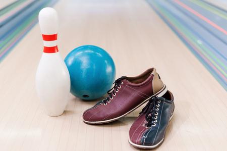 bolos: Primer plano de los zapatos de bolos, bola azul y pines que mienten en la bolera