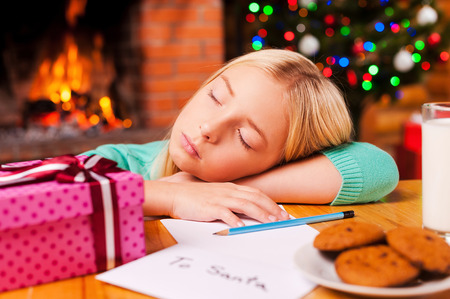Little daydreamer. Cute little girl sleeping while leaning her head at the table with Christmas tree and fireplace in the background