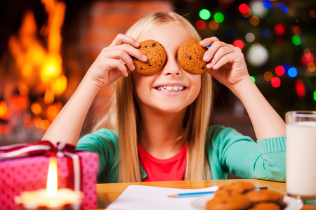 Christmas fun. Cute little girl covering her eyes with cookies and smiling while sitting at the table with Christmas Tree and fireplace in the background photo