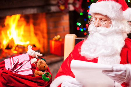 fireplace christmas: Everyone will get a present. Traditional Santa Claus looking at his sack with presents and holding a paper while sitting at his chair with fireplace and Christmas Tree in the background