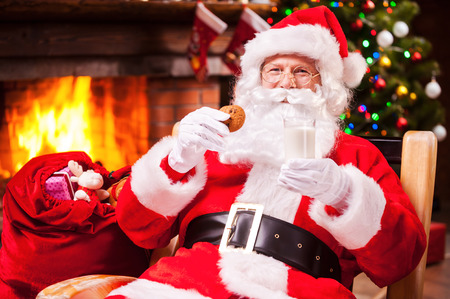 My favorite meal! Cheerful Santa Claus holding glass with milk and cookie while sitting at his chair with fireplace and Christmas Tree in the background