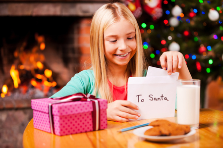 Wish list to Santa. Cute little girl putting a letter to Santa into the envelope while sitting at home with Christmas tree and fireplace in the background photo