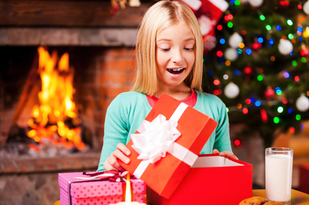 Wow! Cute little girl opening a gift box and smiling while sitting at the table with Christmas Tree and fireplace in the background photo