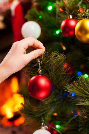 decorating christmas tree: Decorating Christmas Tree. Close-up of child decorating Christmas Tree with Christmas Balls Stock Photo