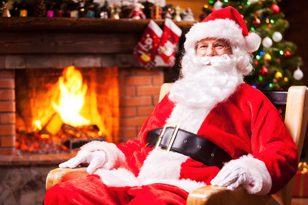headwear: Ho Ho Ho! Traditional Santa Claus sitting at his chair and smiling with fireplace and Christmas Tree in the background