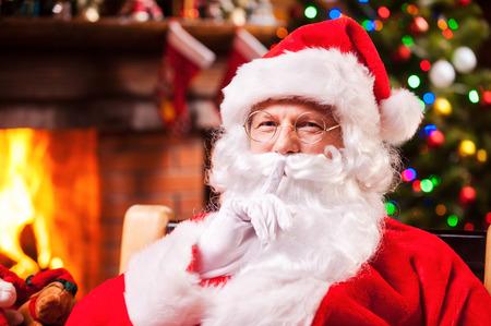 santa clos: Usted no me vio! Pap� Noel tradicional que gesticula la muestra silencio mientras estaba sentado en su silla con chimenea y �rbol de navidad en el fondo