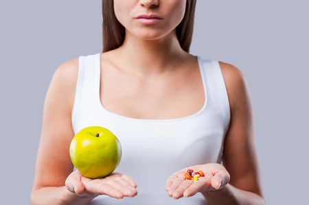 aspirin: Make your choice!  Cropped picture of young woman holding an apple and pills in her hands