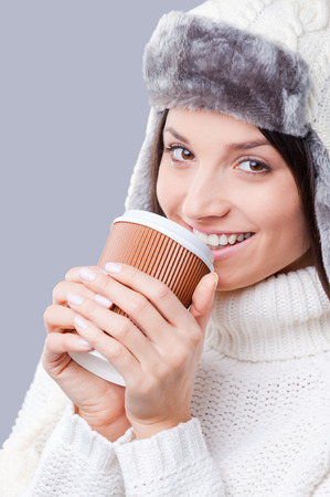 warmness: It is time for warm drinks . Close-up of young women in warm winter clothing drinking coffee and smiling while standing against grey background