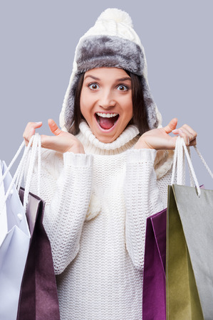 Time for gifts. Happy young women wearing warm winter clothing and holding packages with purchases while standing against grey background photo