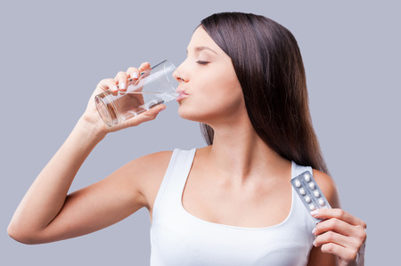 病気の女性。美しい若い女性薬を飲んで目を維持を閉じる
