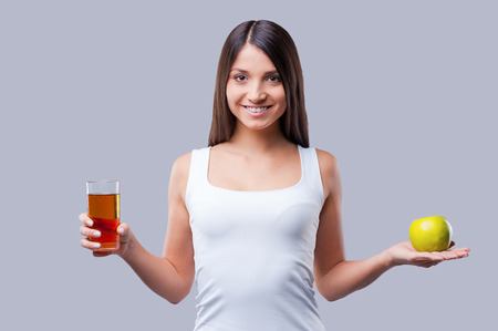 Apple or apple juice? Beautiful young woman holding an apple in one hand and glass with juice in another while standing against grey background photo