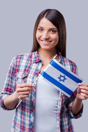 israeli: Beauty with Israeli flag. Happy young women holding flag of Israel while standing against grey background