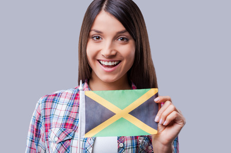 jamaican flag: The are no boundaries for friendship. Happy young women flag of Jamaica while standing against grey background