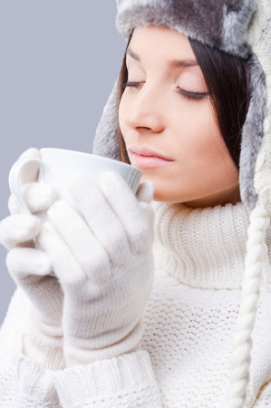 warmness: Winter dreaming. Close-up of young women in warm winter clothing drinking coffee and keeping eyes closed while standing against grey background Stock Photo