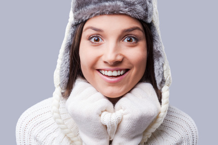 Finally winter comes. Happy young women wearing warm winter clothing while standing against grey background photo