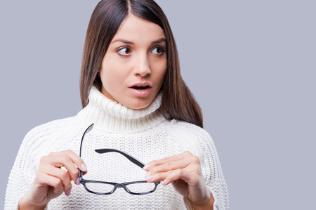 What is that? Shocked young women in warm winter clothing holding glasses while standing against grey background photo