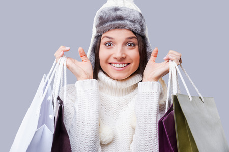 Shopping in any weather . Happy young women wearing warm winter clothing and holding packages with purchases while standing against grey background photo