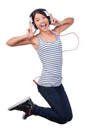 Young and free. Beautiful young woman in headphones jumping against white background photo