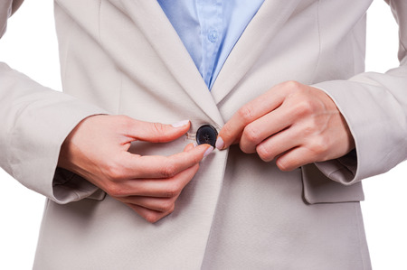 buttoning: Making business look great. Close-up of young businesswoman buttoning her jacket while standing against white background
