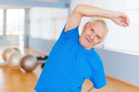 terapia ocupacional: Hombre mayor activo. Hombre mayor alegre que hace ejercicios de estiramiento y sonriendo mientras está de pie en el interior Foto de archivo