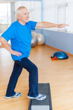 persona de la tercera edad: Mantenerse saludable y activa. Encuadre de cuerpo entero del hombre mayor que hace ejercicios aer�bicos confianza en club de salud Foto de archivo